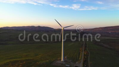 Witte eenwindmolen roteert bij zonsondergang in de bergen en produceert schone energie stock videobeelden