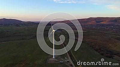 Witte eenwindmolen roteert bij zonsondergang in de bergen en produceert schone energie stock video