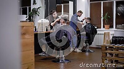Wizerunek wnętrze zakład fryzjerski i dwa fachowego hairstylists Żeńscy i męscy fryzjery męscy pracuje z klientów siedzieć zbiory