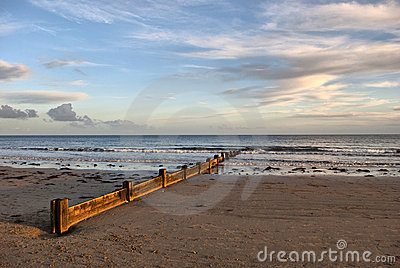 Wodden wave breaker on the beach wit dramatic sky