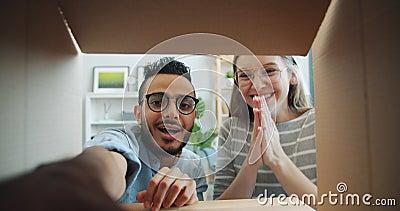 Wolny ruch dziewczyny i faceta otwierającego pudełko kartonowe, zabierającego dar śmiesznie się bawiąc zbiory
