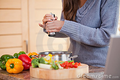 Woman adding pepper to her vegetable stew