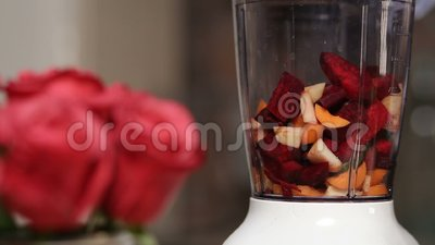 Woman adding vegetables and fruits into blender stock video