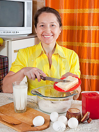 Woman adds margarine into dough