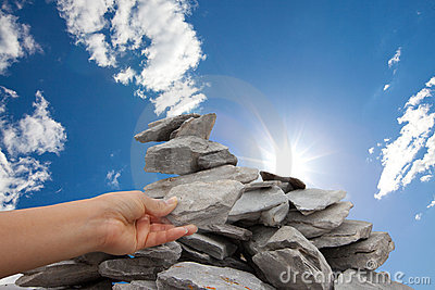 Woman adds rock to cairn under sun filled sky