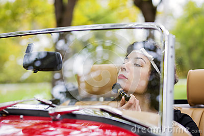 Woman adjust face before mirror at car