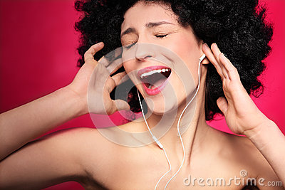 Woman with afro hair enjoying music
