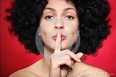 Woman with afro making silence gesture