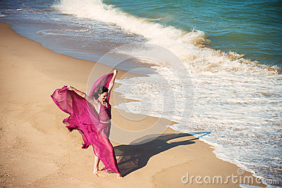 Woman in airy crimson dress on the beach