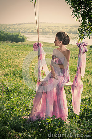 Woman in airy pink dress on the swings