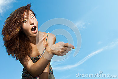 Woman amazed and pointing against the sky