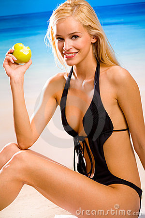 Woman with apple on beach