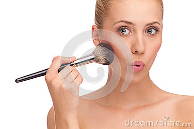 Woman apply powder on a cheek and makes funny face.