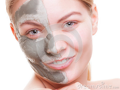 Woman applying clay mask on face. Spa.