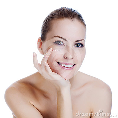 Woman applying cosmetic cream on skin near eyes