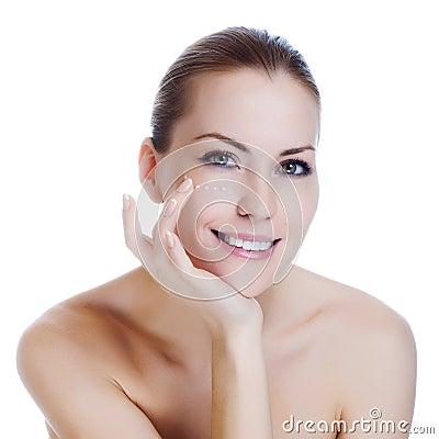 Woman applying cosmetic cream on skin near eyes