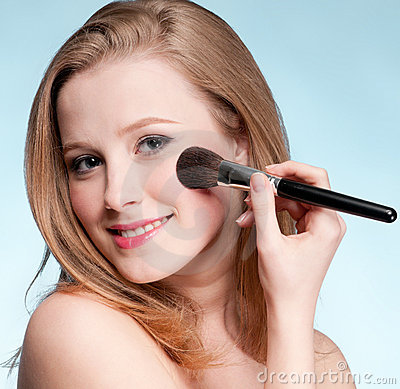 Woman applying cosmetic paint brush