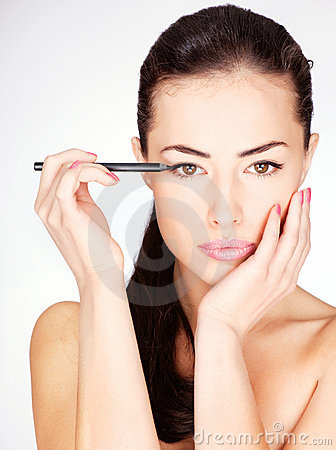 Woman applying cosmetic pencil on eye