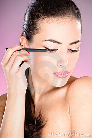 Woman applying cosmetic pencil on eye