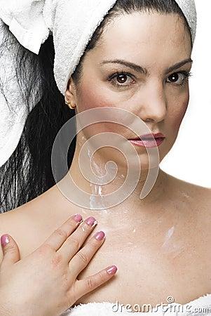 Woman applying cream on body