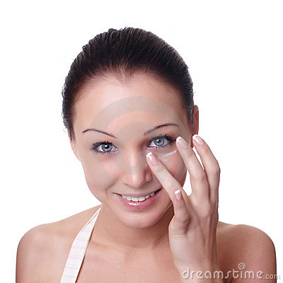 Woman applying creme on face