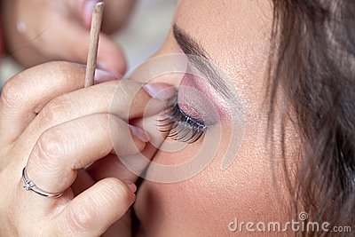 Woman applying eyelashes