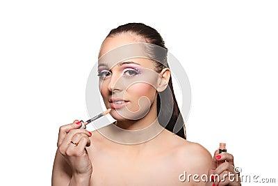 Woman applying gloss for lips.