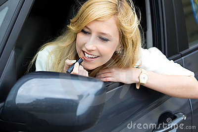 Woman Applying Lipstick in Car Mirror