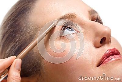 Woman applying make-up using eyebrow pencil