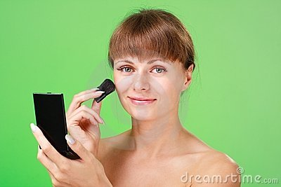 Woman applying makeup on a green background