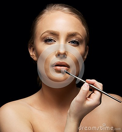 Woman applying makeup on lips