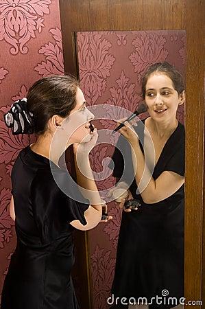 WOMAN APPLYING MAKEUP  looking in the mirror