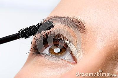 Woman applying mascara on eyelashes