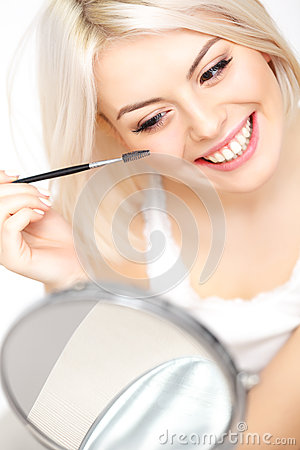 Woman applying mascara on eyelashes. Eye Makeup