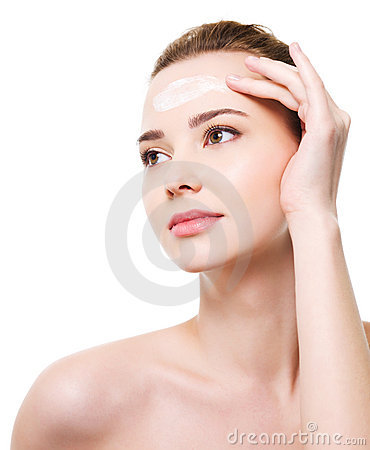 Woman applying moisturizer cosmetic on forehead