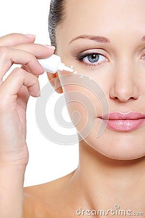 Woman applying moisturizer cosmetic on her eyelid
