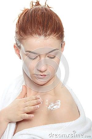 Woman applying moisturizer cream