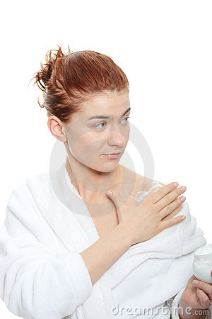 Woman applying moisturizer cream