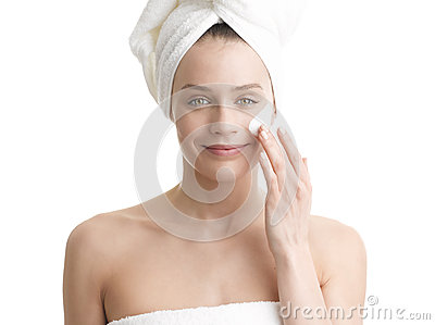 Woman applying moisturizer cream on face