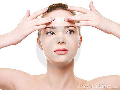 Woman applying moisturizer cream on the forehead