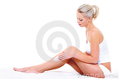 Woman applying moisturizer cream on leg