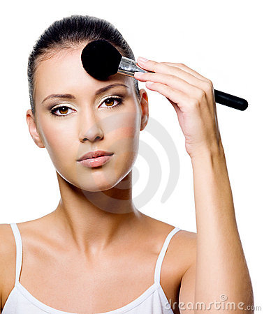 Woman applying powder on forehead with brush