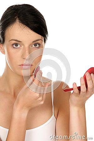 Woman applying rouge on cheek