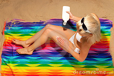 Woman applying sun cream on the beach