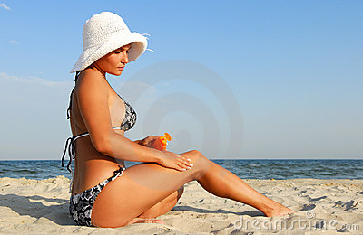 Woman applying suntan lotion