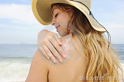 Woman applying suntan lotion at the beach