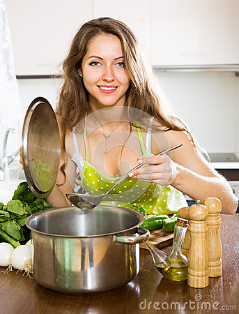 Woman in apron cooking soup