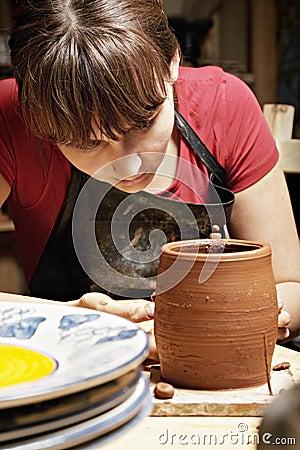 Woman in apron looking at jug