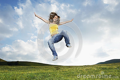 Woman With Arms Outstretched Screaming While Jumping In Park