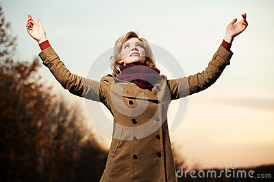 Woman with arms raised against a sky